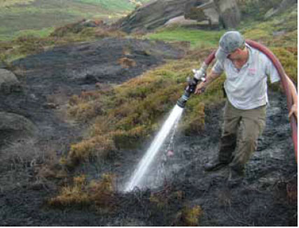 Photo B8.10 A Ranger assisting with damping down hot spots at a fire in the Peak District