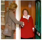 Two women shaking hands at a front door