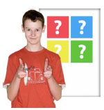 A boy pointing forward in front of a poster with question marks on it