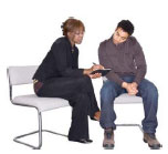 Man and woman sitting on chairs looking through written information