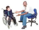 Man sitting on a chair talking to a man in a wheelchair