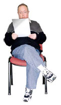 Photo of a man with learning disabilities sitting on a chair reading a pamphlet