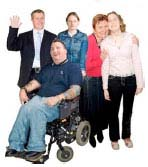 Family and carers with man in a wheelchair