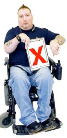 Man in a wheelchair holding a clipboard with a red cross on it