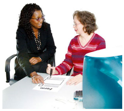 Two women sitting at a desk completing a form