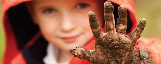 Child holding up his muddy hand