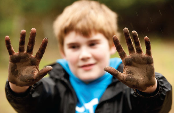Child holding up both hands which are covered in mud
