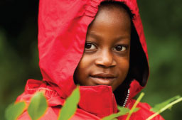 Child wearing a red jacket with their hood up